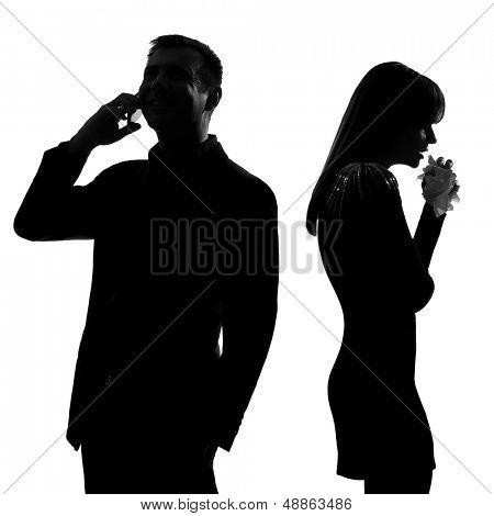 un hombre de espalda con espalda caucásica par permanente en el teléfono y la mujer llorando en silueta de estudio