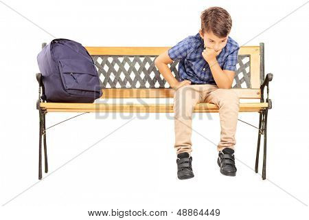 School boy sitting on a bench and thinking, isolated on white background