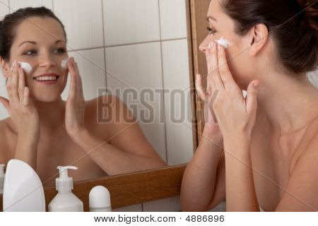 Body Care Series - Young Woman Applying Cream In The Bathroom