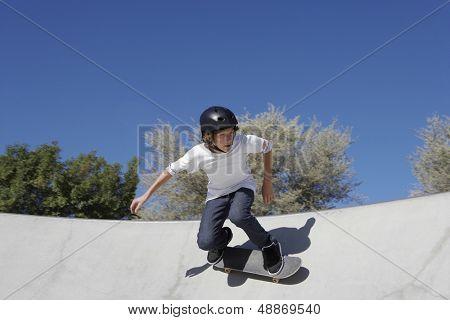 Teenage boy in skateboard park against blue sky