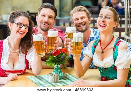 Friends in traditional Bavarian Tracht in restaurant or pub drinking beer in Bavaria, Germany