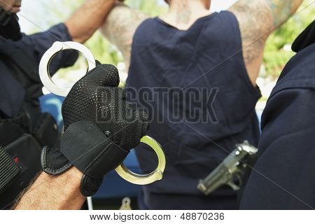 Cropped image of policemen arresting criminal