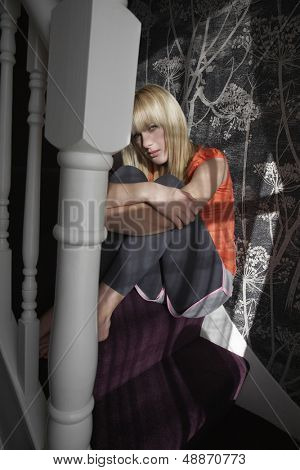 Full length portrait of lonely teenage girl hugging knees on steps at home
