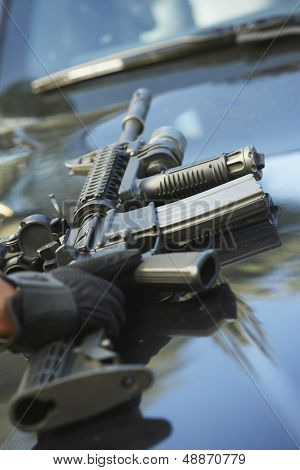 Closeup of policeman's hand picking up gun from car hood