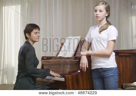 Girl singing accompanied by teacher playing piano