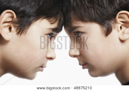 Closeup of preadolescent siblings with head to head isolated over white background