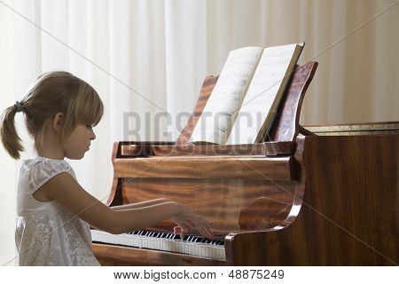 Side view of a young girl playing the piano