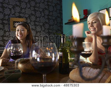 Sonriendo a multiétnicas jóvenes disfrutando la cena