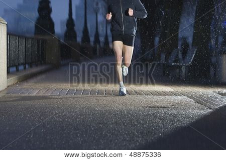 Lowsection of a man jogging on city pavement at dawn n London