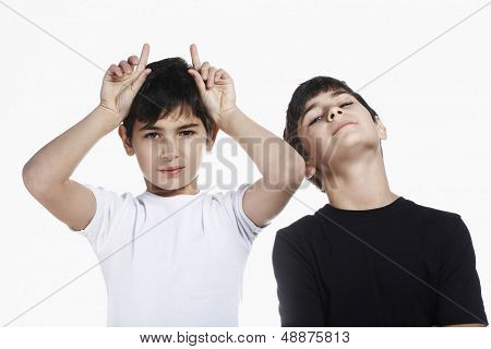Portrait of preadolescent boy showing rude gesture while standing with brother isolated over white background