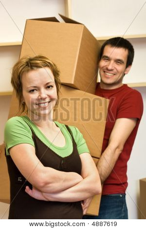 Happy Couple Moving - Carrying Boxes