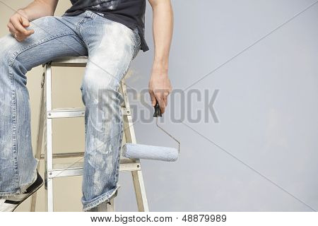 Midsection of man holding paintroller while sitting on stepladder against wall