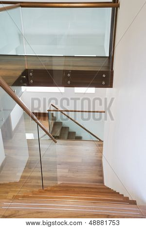 View of wooden stairs with glass banisters in house