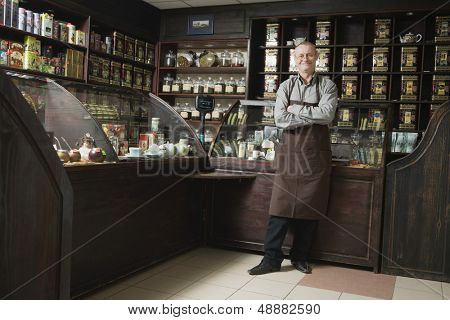 Full length portrait of senior male owner standing in shop
