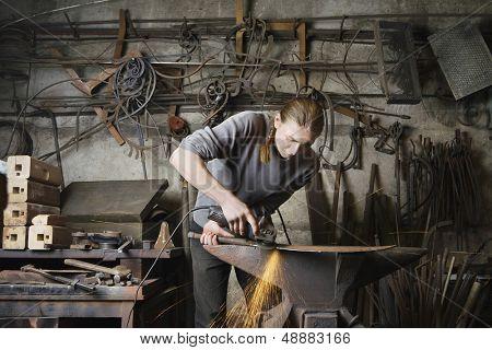 Joven macho Herrero trabajando en taller