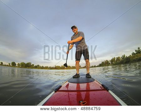 mature male paddler enjoying workout on stand up paddleboard (SUP), calm lake in Colorado, summer