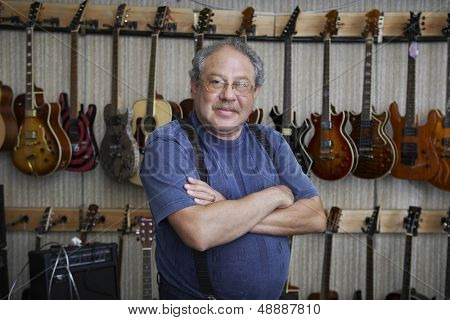 Portrait of middle aged male music store owner standing arms crossed