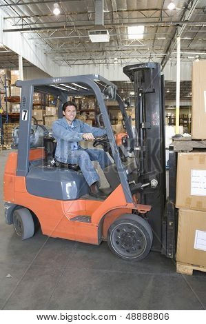 Portrait of a smiling man operating forklift truck in distribution warehouse