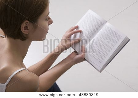 Closeup of a cropped young woman reading book against gray background