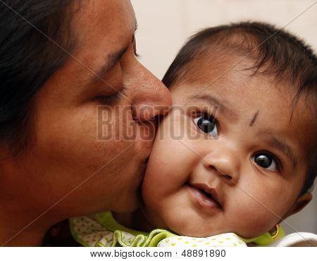Mother Expressing Love To Daughter By Kissing The Child