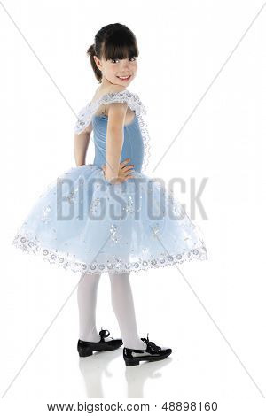 A happy little tap dancer looking back at the viewer in her beautiful blue dance dress.  On a white background.