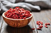 stock photo of berries  - wooden bowl with goji berries on the table closeup - JPG