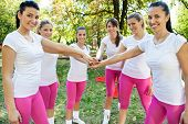 stock photo of huddle  - Sportswomen with hands together in huddle - JPG