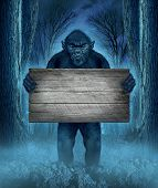stock photo of creepy  - Monster holding a rustic blank old wood sign as a creepy halloween concept with a werewolf lurking as a bigfoot creature coming out of a dark scary background with a moon glow behind it as a horror symbol of a haunted woods animal - JPG