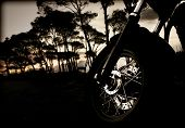 stock photo of chopper  - Closeup photo of motorcycle wheel on sunset - JPG