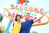 Las vegas people - couple happy cheering by sign. Welcome to Las Vegas sign billboard and excited ch