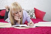 Постер, плакат: Полная длина красивых подростков студента писать в книге лежа на кровати