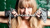 stock photo of sado-masochism  - beautiful woman with a steel chain in his mouth against the wall - JPG