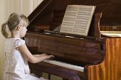 stock photo of ponytail  - Side view of a young girl playing the piano - JPG