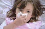stock photo of temperature  - Sick little girl sneezing in bed - JPG
