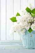 stock photo of vase flowers  - Bouquet of white lilac spring flowers in a wooden blue vase on light shabby chic background - JPG