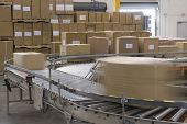 image of warehouse  - Cardboard boxes on conveyor belt in distribution warehouse - JPG