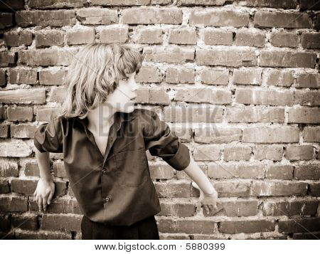 Young boy is in front of a brick wall