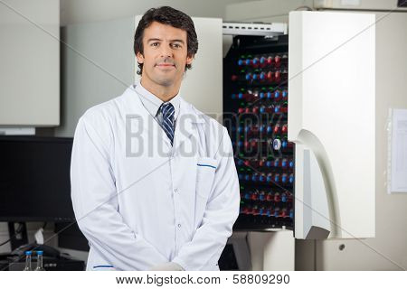 Portrait of confident male researcher standing by blood culture instrument in lab