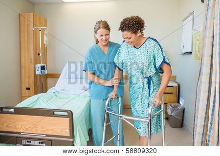 Mid adult female nurse helping patient to walk using walker in hospital