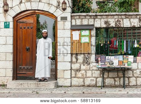 SARAJEVO, BOSNIA AND HERZEGOVINA - AUGUST 13, 2012: Religious Muslim man stands in doorway on street close to main mosque in old town Sarajevo.