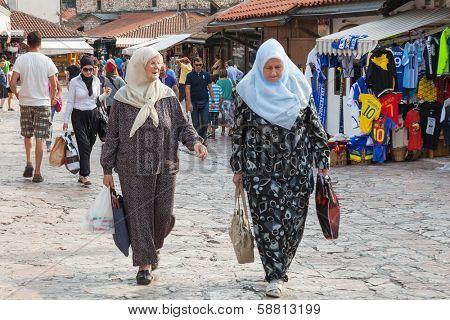 SARAJEVO, BOSNIA AND HERZEGOVINA - AUGUST 13, 2012: Muslim women walk on Bascarsija, the old town. Sarajevo has a mixture of muslim, catholic and orthodox population.