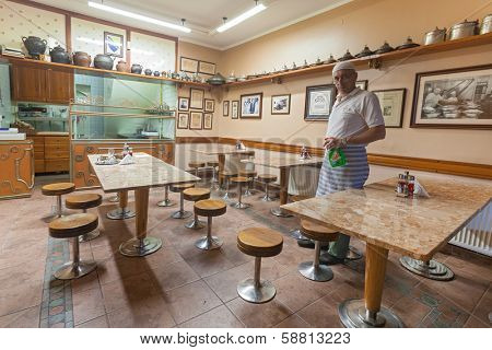 SARAJEVO, BOSNIA AND HERZEGOVINA - AUGUST 13, 2012: Owner cleans restaurant tables after long day at work in old town Sarajevo.