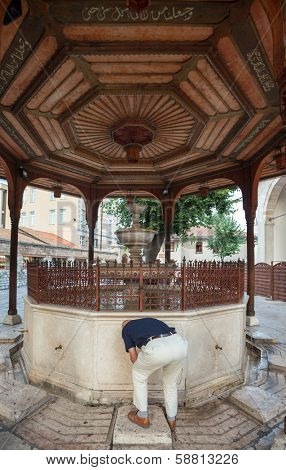 SARAJEVO, BOSNIA AND HERZEGOVINA - AUGUST 13, 2012: Man drinking water from fountain on the the Sadirvan (ablutions fountain) of the Gazi Husrev-Beg Mosque, Sarajevo's most popular mosque.