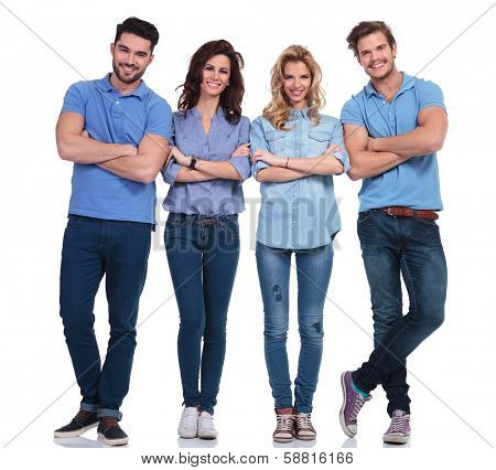 full body picture of four casual young people with hands folded standing on white background and smile