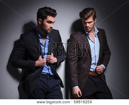 two hot male models posing against studio background, one looking away and one pulling his suit's collar