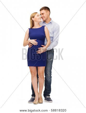 pregnancy, parenthood and happiness concept - happy young family expecting child looking at each other