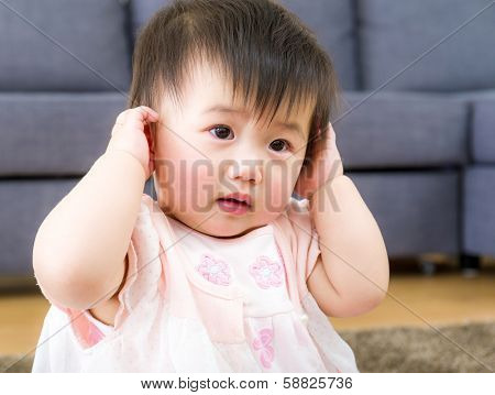 Little girl using hand to cover ear