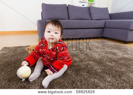 Baby girl sitting on carpet with water bottom and doll