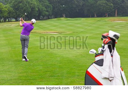 A golfer playing a mid iron fairway shot into the green on a par 4 hole, series of 3. Focus is on the golfer.