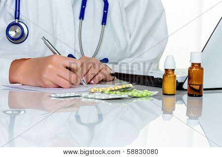 doctor writes a prescription for tablets. in the doctor's office